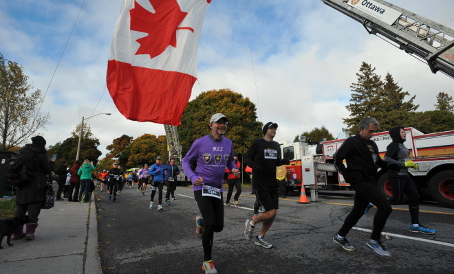 Participants run by firetruck with Canadian flag
