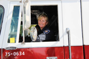 Female firefighter in uniform smiling while sitting in large firetruck.