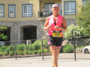 Female runner, wearing a pink shirt and black shorts. Runner is 50 years old, blonde, wearing a hat to shield off the sun as she competes in a race. She's wearing a yellow race bib on her pink shirt. She is mid stride running and looks happy.